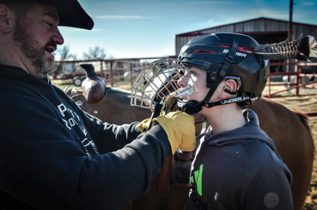 Since his accident last year, Dane Lancaster wears a helmet every time he rides a horse. His father, Diran, helps adjust the straps. Dane even recorded a video PSA about the necessity of wearing helmets in equestrian sports. View it at www.facebook.com/prayersfordane. Messenger Photo by Joe Duty